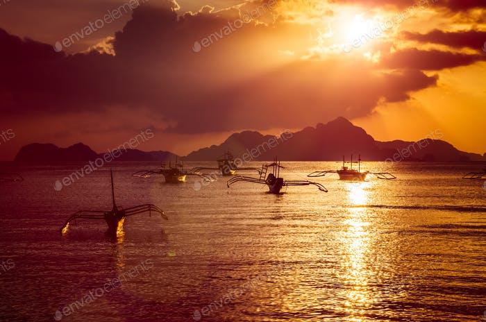Traditional filippino boats at El Nido bay in sunset lights. Palawan island, Philippines