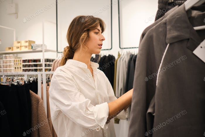 Young beautiful fashion designer confidently working in showroom