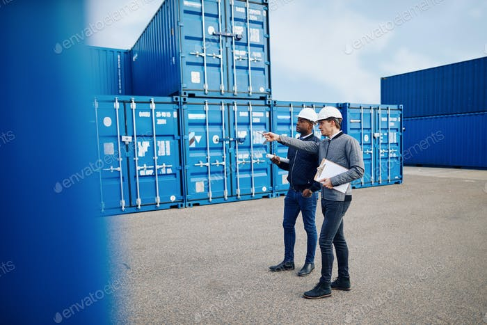 Two engineers tracking shipping inventory in a freight container yard