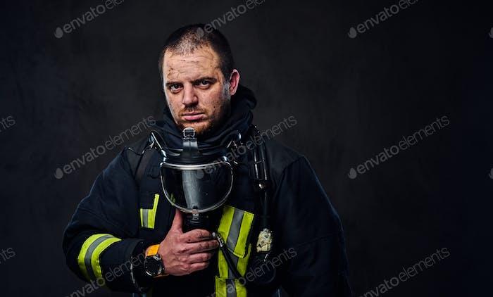 Studio portrait of a male dressed in a firefighter uniform.