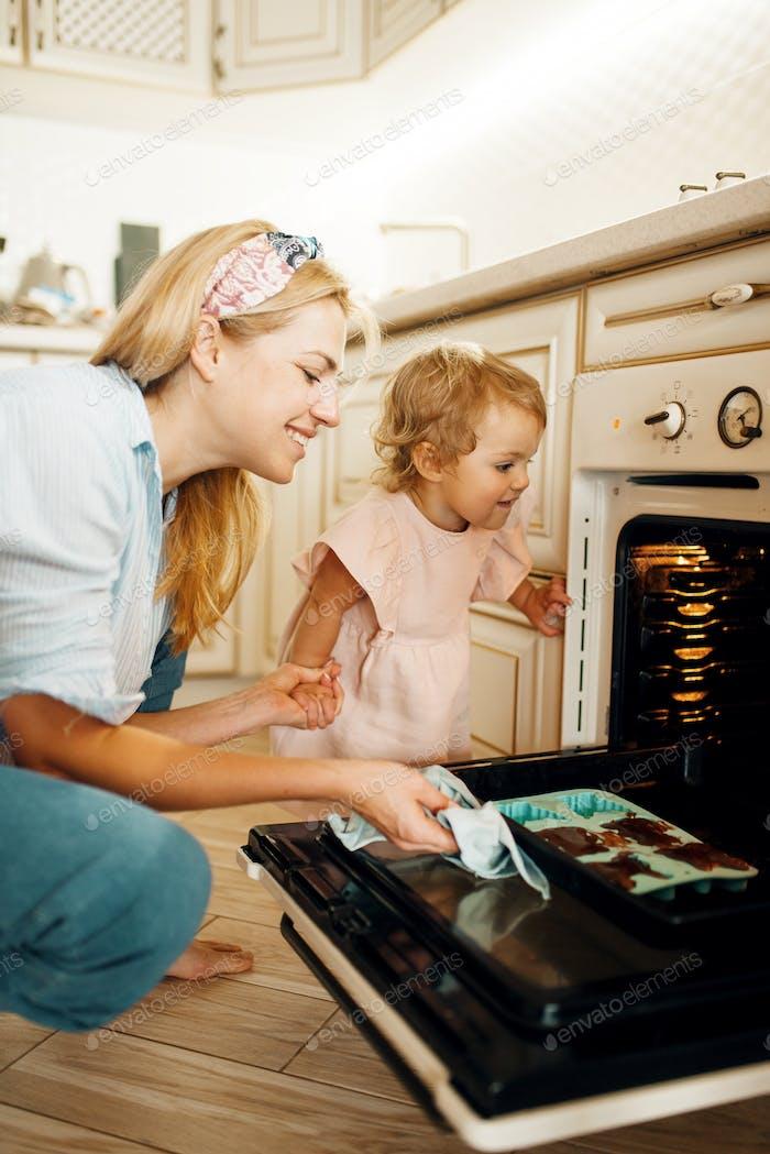 Mutter und Kind aus dem Ofen Backblech entfernen