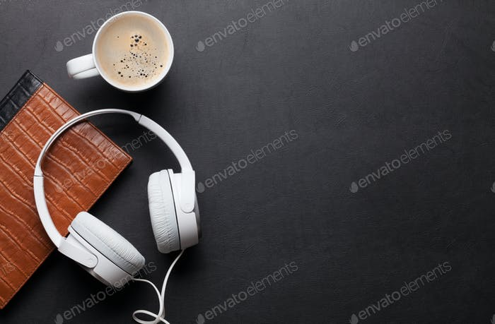 Office desk table with notepad, headphones, coffee