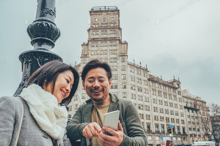 Asian tourist couple looking at the mobile phone