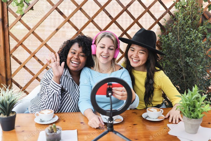 Multiracial friends streaming online with mobile phone camera - Focus on faces