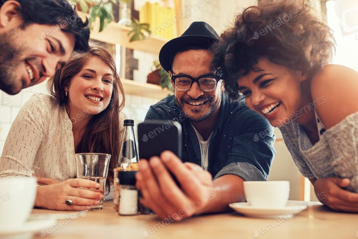 Friends watching photos on mobile phone