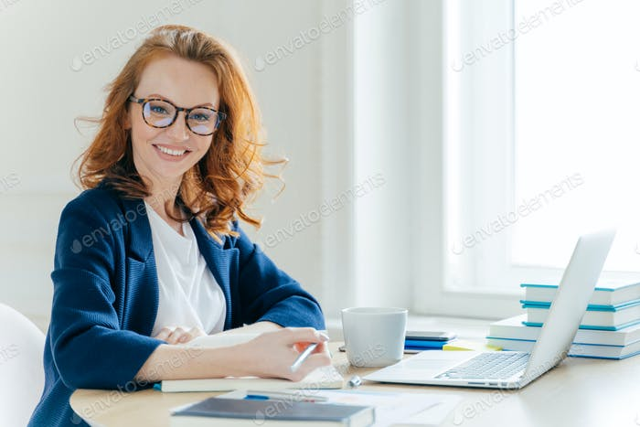Self confident young female director plans work process, writes main theses in notepad