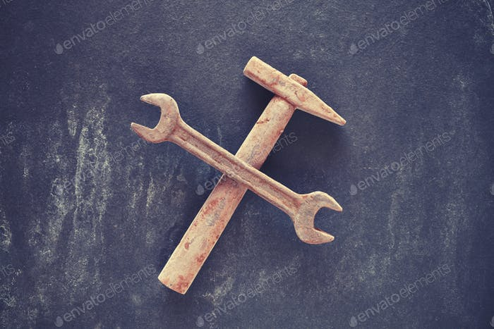 Rusty like crossed wrench and hammer.