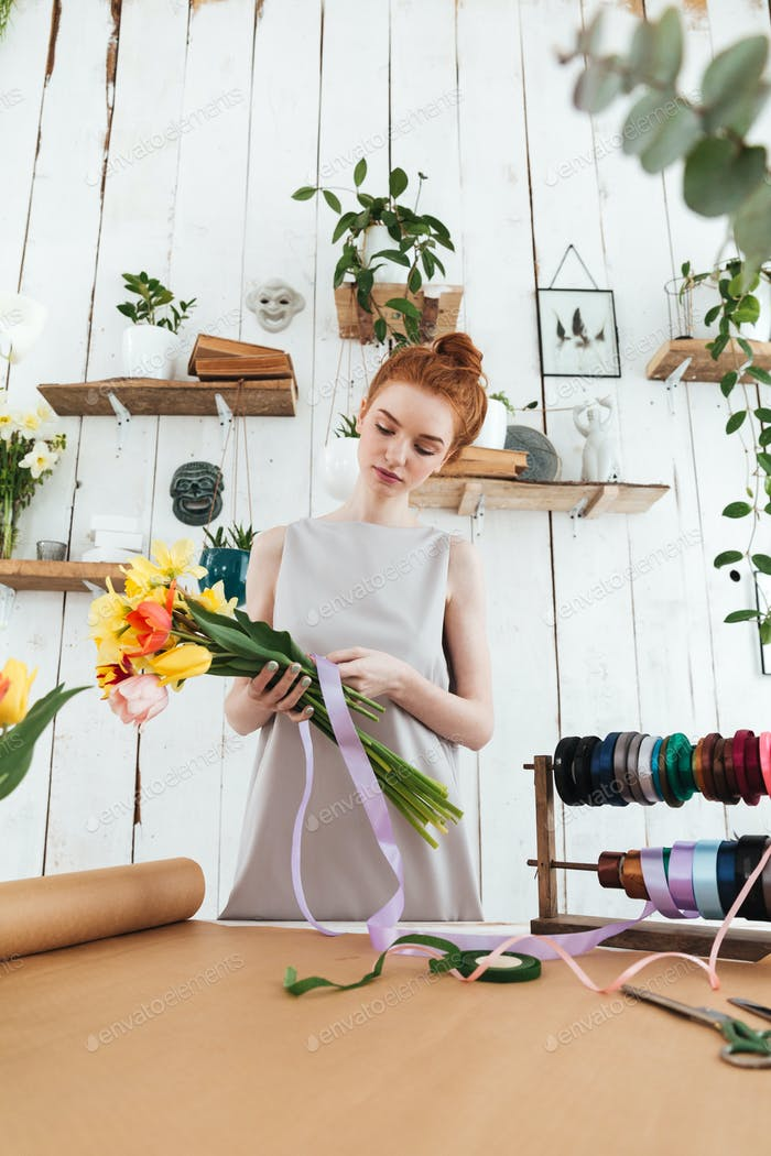 Redhead lady florist collecting bouquet while standing near table