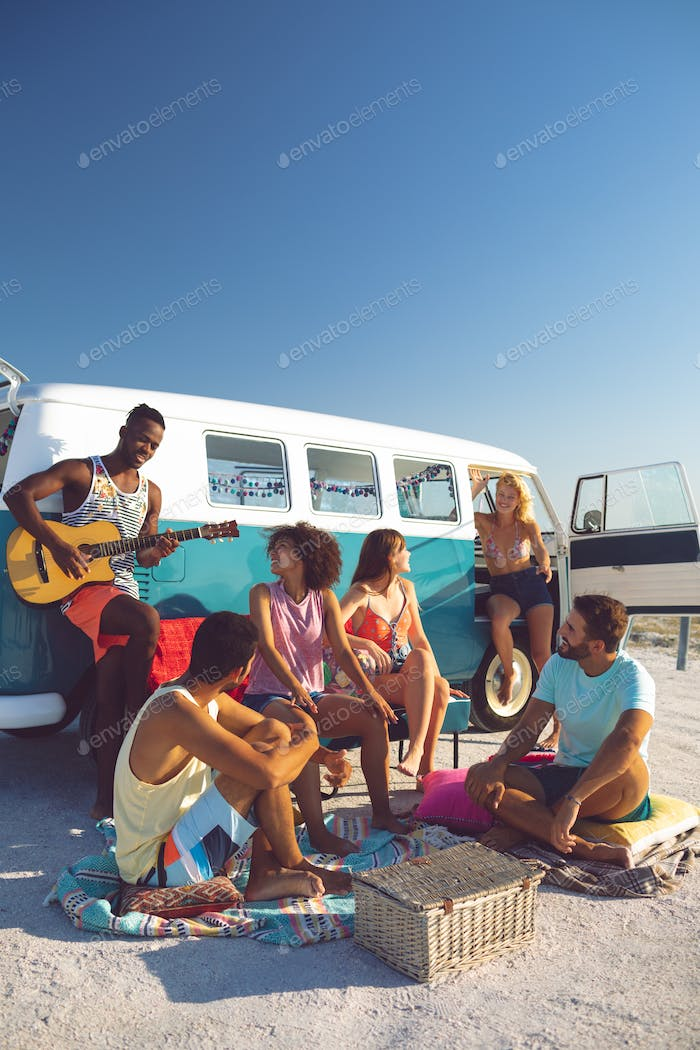 Front view of young group of diverse friends having fun near camper van at beach