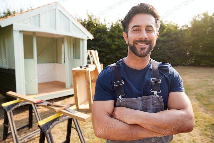 Portrait Of Male Carpenter Building Outdoor Summerhouse In Garden
