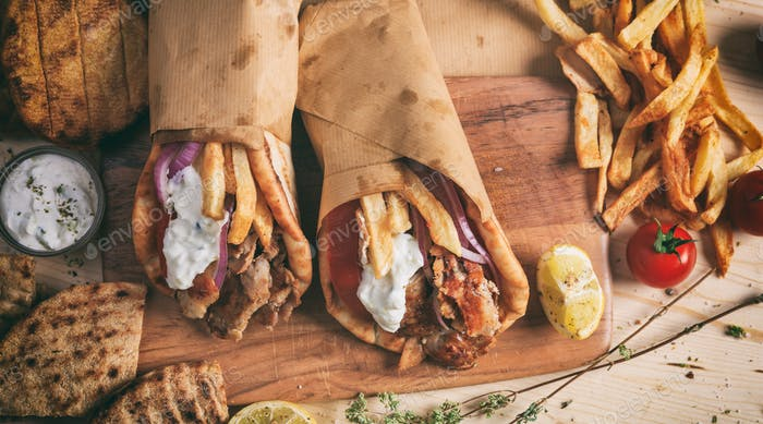 Greek gyros wrapped in pita breads on a wooden table - top view