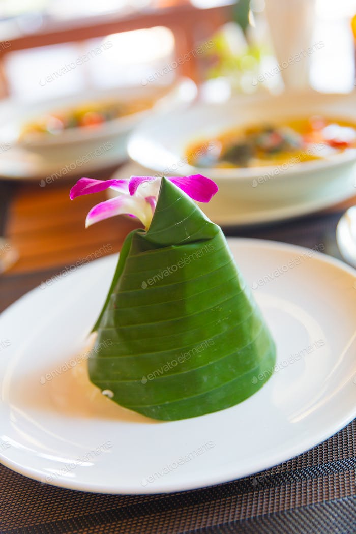 Steam Rice Wrapped In Cone Shape Banana Leaf With Orchid