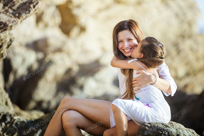 Happy young mother and daughter hugging