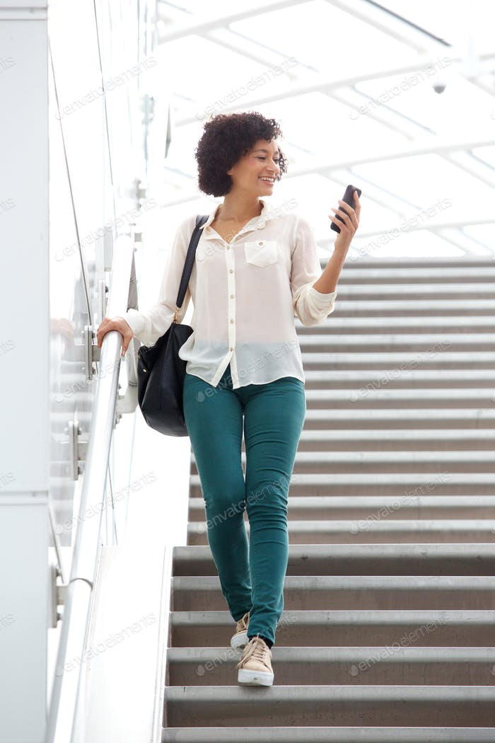 woman in 30s walking downstairs with mobile phone