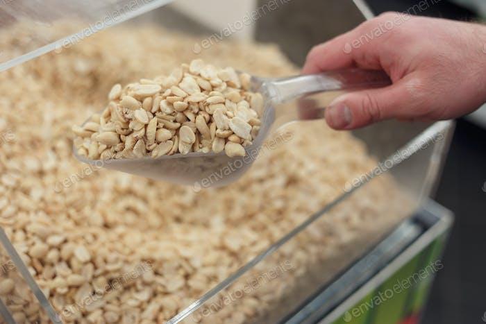 Mens mano recoja cacahuetes tostados salados con una espátula en una tienda.