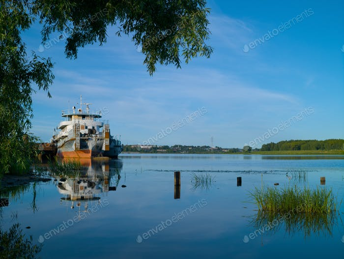 Old river tug stands in river backwater summer sunny morning