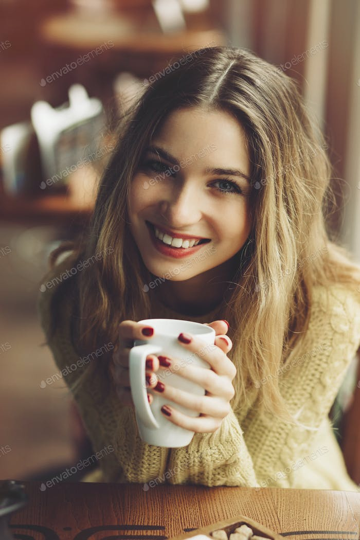 Charmantes Mädchen trinken Cappuccino und Essen Käsekuchen