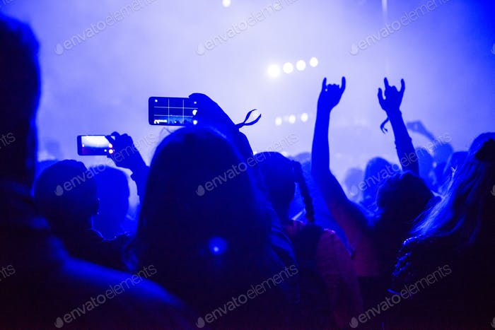 Silhouette of hands recording a concert with smart phones