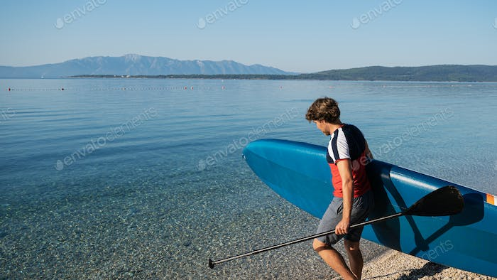 Young man carrying sup board
