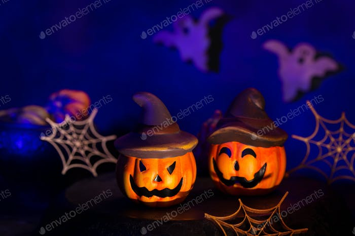 Halloween composition with pumpkins, scary ghosts and spider webs