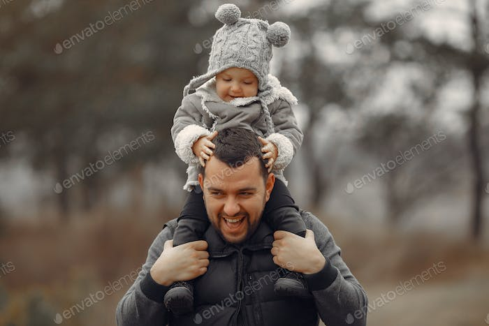 Father with little daughter playing in a spring field