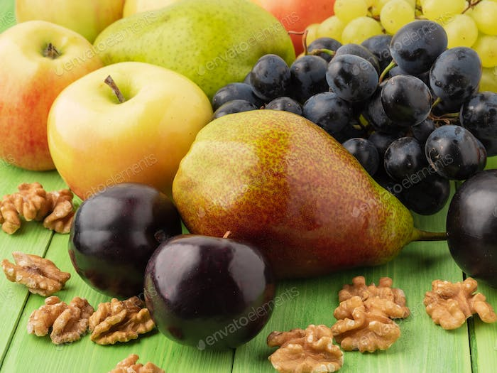 set of fruits on a green wooden table - apples, pears, grapes, plums, walnuts