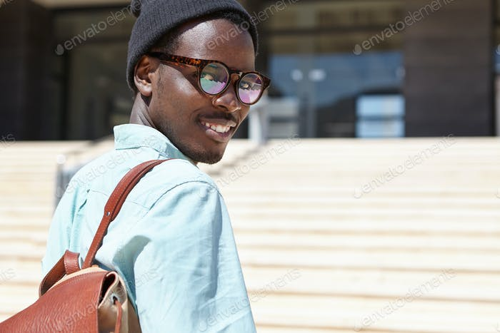 Outdoor portrait of young Afro American traveler with knapsack standing on concrete stairs, going to