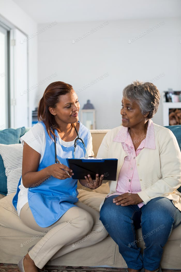 Doctor explaining medication on clipboard to senior woman in living room