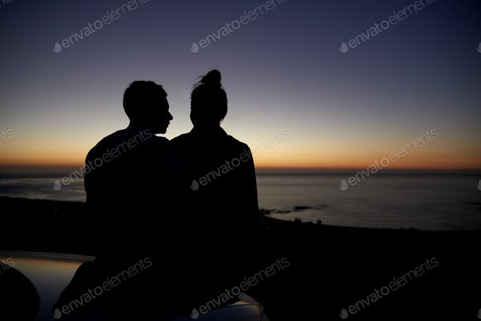 Couple relaxing by the sea at sunset by a car, silhouette
