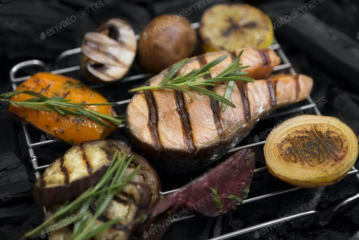 Grilled fish with rosemary and vegetables on grid