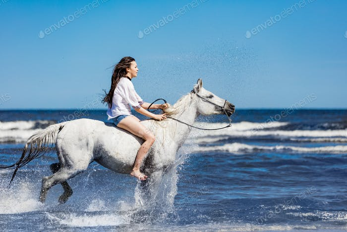 Young girl riding on the white horse through the ocean.