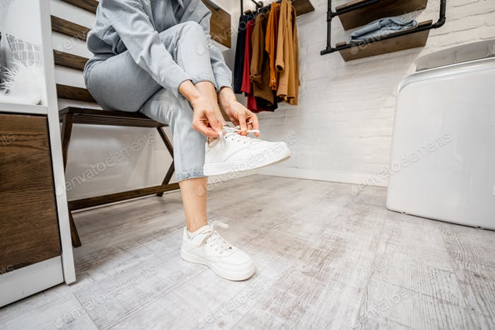 Woman wearing white sneakers indoors