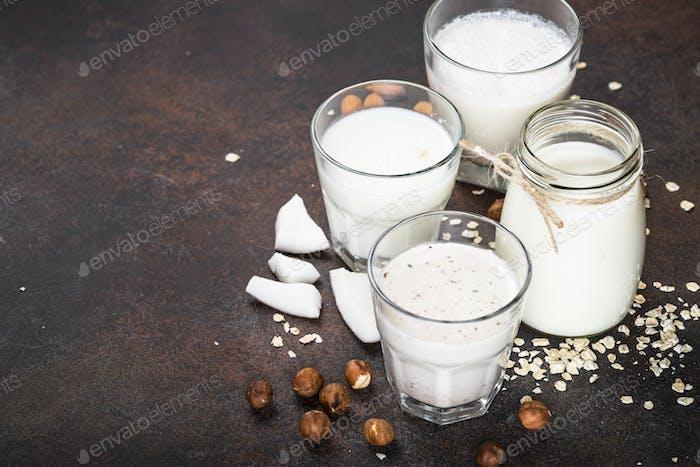 Vegane, nicht milchige Alternativmilch auf dunklem rostigen Tisch