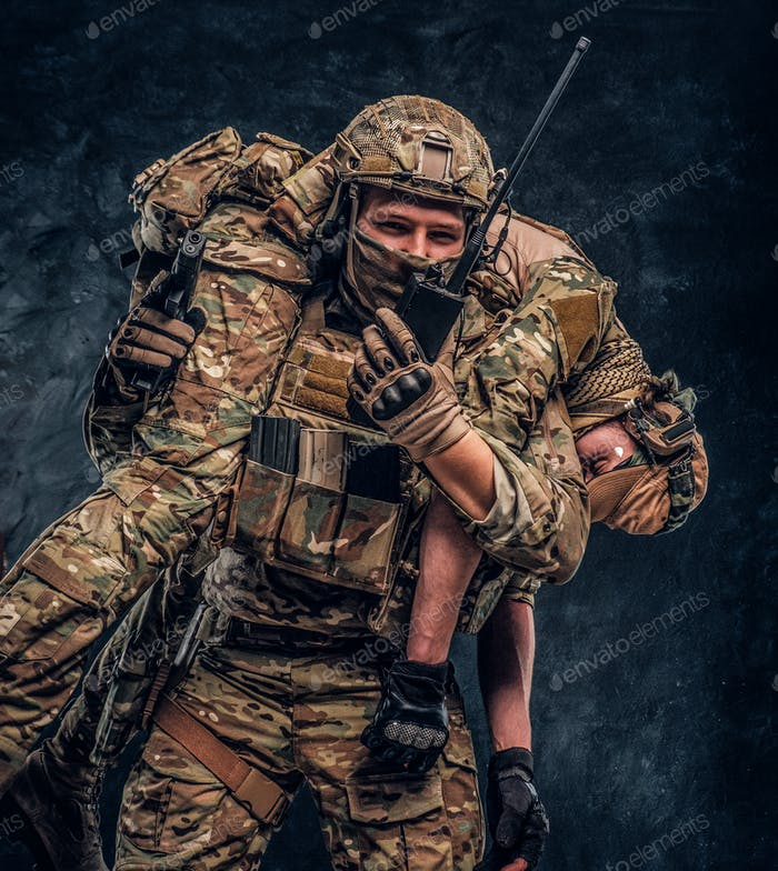 Military medic rescues his wounded teammate carrying him off the battlefield