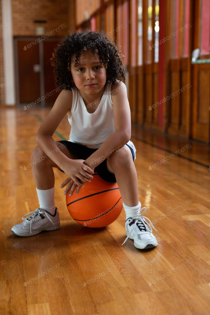 Schoolboy sitting on basketball and looking at camera in basketball court at school