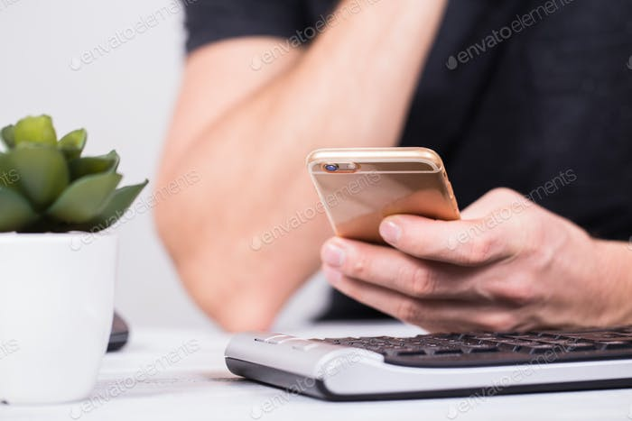 Hands of businessman using a mobile phone and keyboard