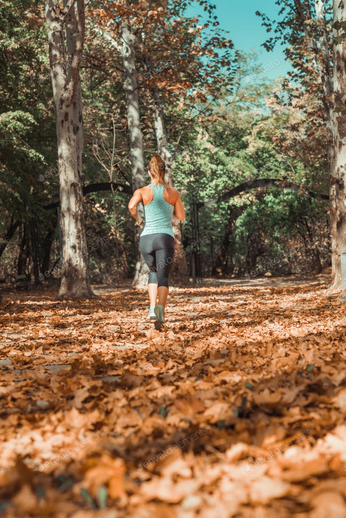 Woman Jogging Outdoors in The Fall