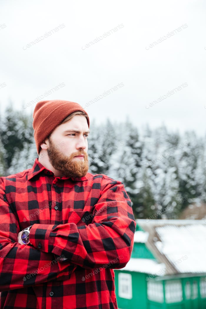 Serious bearded young man standing with hands folded  in winter