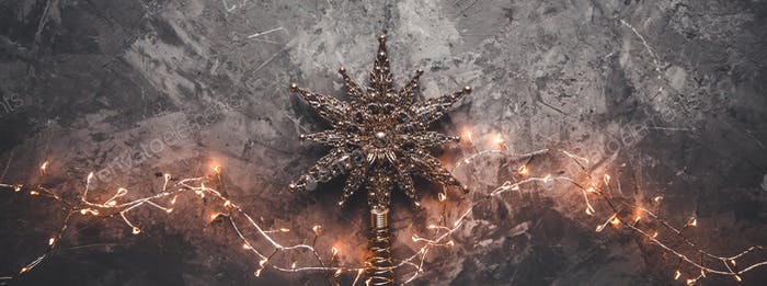 Weihnachtsstern auf grauem Hintergrund mit Girlanden. Neujahrslandschaft