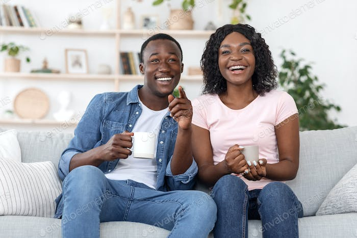 Joyful african couple drinking tea and watching movie
