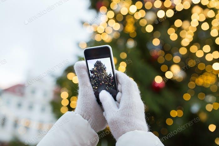 Hände mit Smartphone fotografieren Weihnachtsbaum