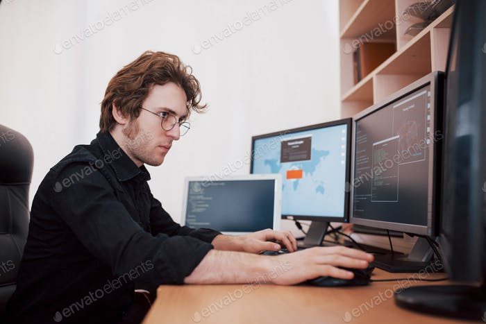 Male programmer working on desktop computer with many monitors at office in software develop company