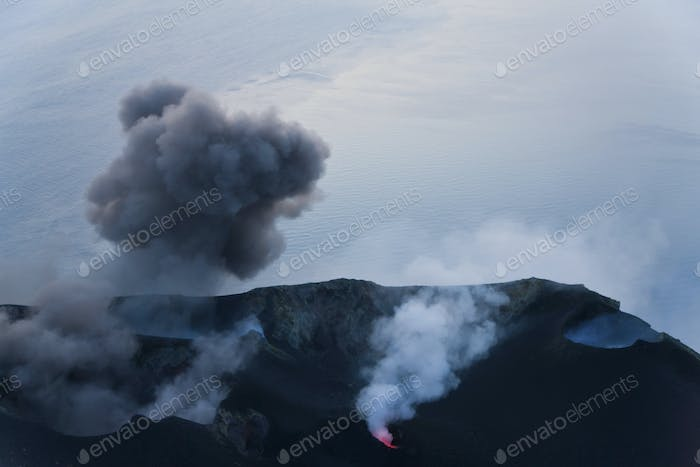 Plumes of smoke and lava emanating from a volcano.