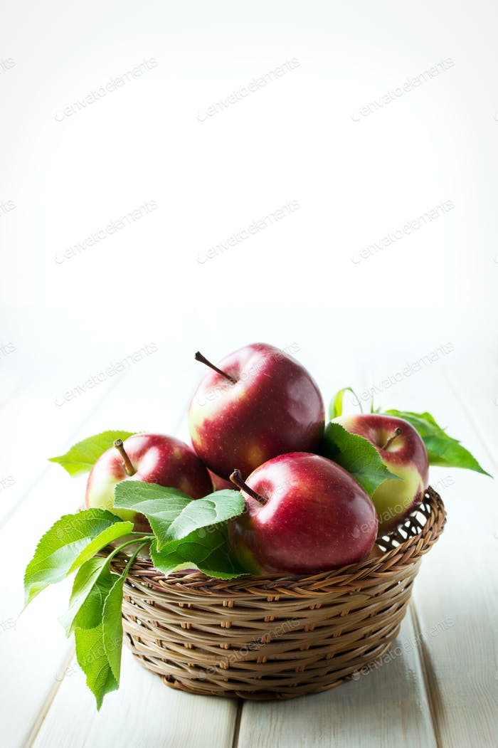Organic apples with leaves in  basket