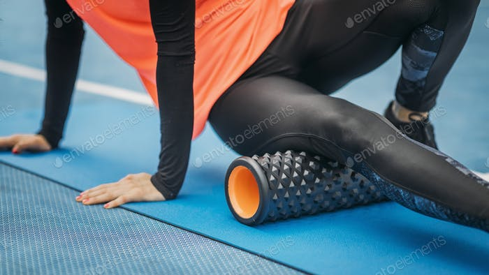 Female Athlete using Foam Roller