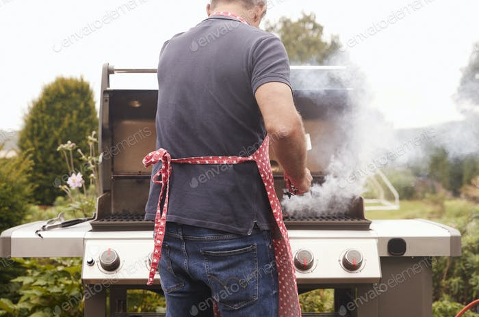Middle aged man burning food on a barbecue, back view
