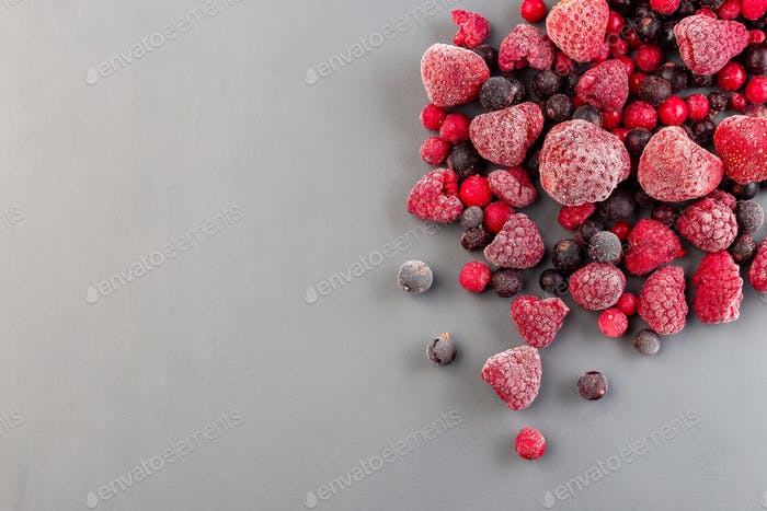 Frozen berries on gray background, copy space, top view