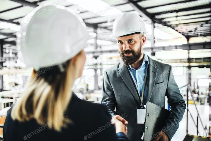 Ein Porträt eines Industriemannes und einer Ingenieurin in einer Fabrik, die die Hände schüttelt.