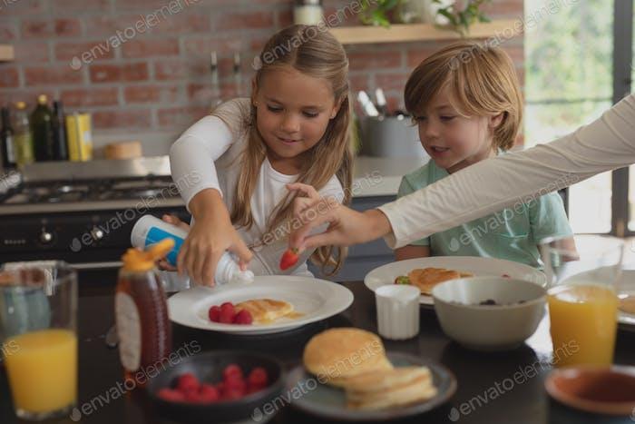 Vorderansicht der kaukasischen Geschwister mit Essen am Esstisch in einem komfortablen Haus