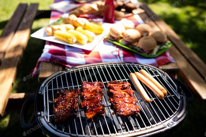 Barbeque with buns and corn on table in park